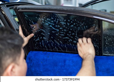Penang, Malaysia - January 21, 2020 : Car window tinting specialist attaching vinyl tinting film to car side window.