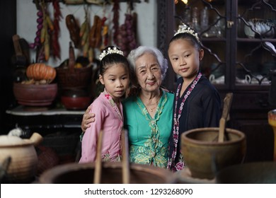 Penang, Malaysia - January, 22 2019: A beautiful old woman model posing with two young girls. Chinese traditional clothing and house can be found in Peranakan Mansion in Penang.