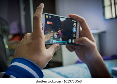 PENANG, MALAYSIA- JANUARY 31, 2018: Playing mobile games while laying on bed is so much relaxing.