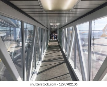 Penang, Malaysia - January 5, 2019 : View of a passenger walking on a jet bridge heading to an airplane at Penang International Airport