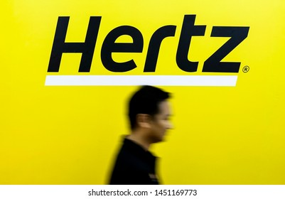 PENANG, MALAYSIA - JULY 05, 2019 : Man walk across the Hertz logo on a wall at customer service center. Hertz is an American car rental company with international locations in 145 countries worldwide.