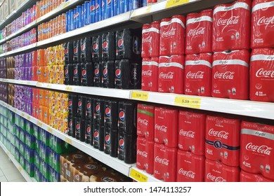PENANG, MALAYSIA - JULY 11, 2019: Row of various brand carbonated drinks on display in a grocery store. Carbonated drinks are beverages that contain dissolved carbon dioxide.