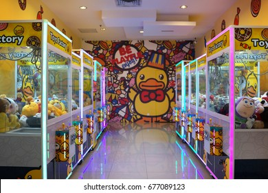 PENANG, MALAYSIA - JULY 13, 2017 : Arcade crane vending machine with colourful  lights at the game centre. The dolls sold in coin operating machine by using clamp to pull the toy up.