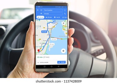 Penang, Malaysia - July 17, 2018: Female using Google Maps service on smartphone in car. Google Maps is most popular mapping service for mobile provided by Google.