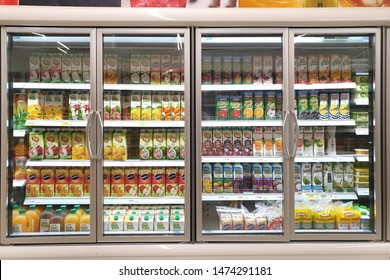 PENANG, MALAYSIA - JULY 23, 2019: Interior view of huge glass freezer with various brand beverage in Tesco store. Tesco is a British multinational groceries, retail and consumer services chain.