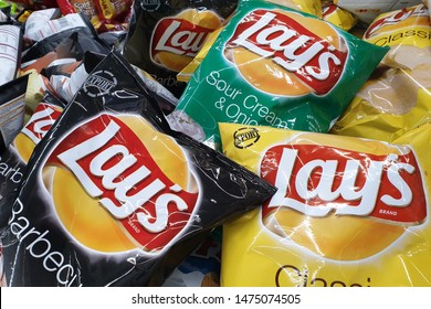 PENANG, MALAYSIA - JULY 23, 2019: Top view various flavoured of lay's potato chips for sale in grocery store. Lay's has been owned by PepsiCo through Frito-Lay since 1965.