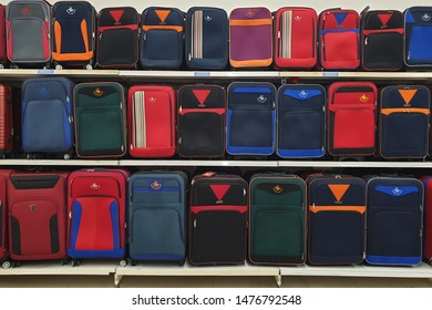 PENANG, MALAYSIA - JULY 23, 2019: Rows of multicolor travel luggage on store shelf in Tesco hypermarket. Tesco is the third largest retailer stores worldwide, British multinational grocery retailer.