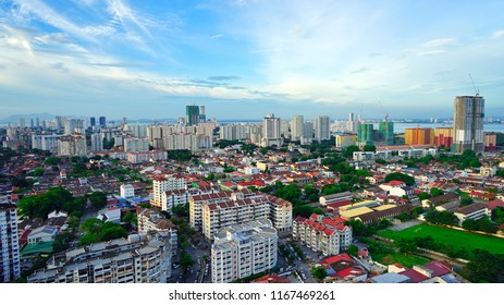 Penang, Malaysia - June 1st 2018: An aerial sunset view of residential houses against backdrop of new high rise condominiums in Jelutong district.