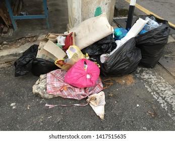 Penang, Malaysia - June 4, 2019 : Bags of garbage being thrown by a roadside haphazardly at Armenian Street Penang