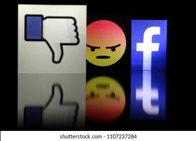 PENANG, MALAYSIA - JUNE 6, 2018: Facebook security and privacy issues. Close up Facebook logo with the dislike icon and angry face emoji behind it on black background.