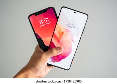 PENANG, MALAYSIA - MAR 11, 2021: Hand holding Samsung Galaxy S21 Ultra 5G front view comparison with Apple iPhone 11 pro max in isolated white background