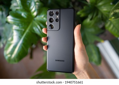 PENANG, MALAYSIA - MAR 11, 2021: Hand holding the latest Samsung Galaxy S21 Ultra 5G Phantom Black color and showing the back of the phone and brand new camera lens in green leaf background