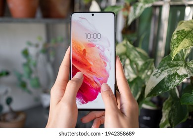 PENANG, MALAYSIA - MAR 11, 2021: Hand holing the latest Samsung Galaxy S21 Ultra 5G Phantom Black color and showing the front screen in green leafs and pots background