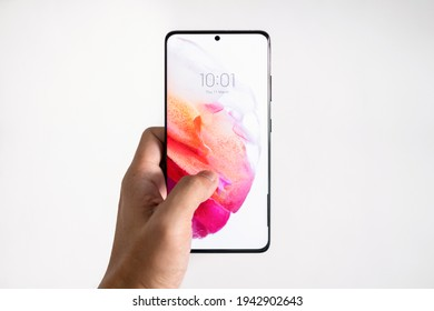PENANG, MALAYSIA - MAR 11, 2021: Hand holing the latest Samsung Galaxy S21 Ultra 5G Phantom Black color and showing the front screen in isolated white background