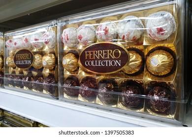PENANG, MALAYSIA - MAR 15, 2019: Ferrero Rocher premium chocolate in transparent plastic box on store shelf. Ferrero Rocher is a spherical chocolate produced by the Italian chocolatier Ferrero SpA.