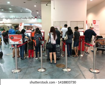 PENANG, MALAYSIA, March 11, 2019: Flight passenger queuing to use convenient self check-in kiosk machine at Penang International Airport facility to check in their flight