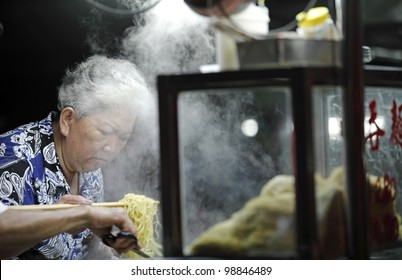 PENANG, MALAYSIA - MARCH 23: Street vendor with her noodle stall on March 23, 2012 in Lebuh Chulia, Penang, Malaysia. The hawker is located at Lebuh Chulia street which is a UNESCO heritage site.