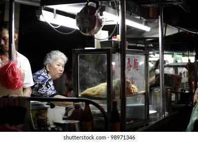 PENANG, MALAYSIA - MARCH 23: Street vendor at her noodle stall on March 23, 2012 in Lebuh Chulia, Penang, Malaysia. The hawker stall is located at Lebuh Chulia street which is a UNESCO heritage site.