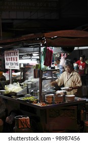 PENANG, MALAYSIA - MARCH 23: Street food vendor at his noodle stall on March 23, 2012 in Lebuh Chulia, Penang, Malaysia. The hawker is located at Lebuh Chulia street which is a UNESCO heritage site.