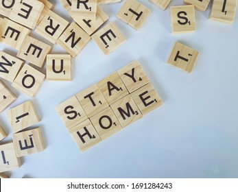 """Penang, Malaysia - March 29, 2020: Scrabble game letters on white background. Words """"STAY HOME"""" on scrabble alphabet tiles."""