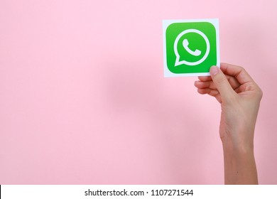 PENANG, MALAYSIA - MARCH 30, 2018: Close up female hand holding a printed card with the WhatsApp logo on pink background.