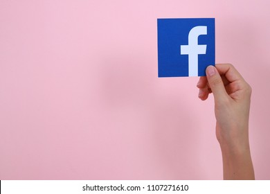 PENANG, MALAYSIA - MARCH 30, 2018: Close up female hand holding a printed card with the Facebook logo on pink background.