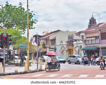 Penang, Malaysia - May 12, 2017: Trishaw at the junction of Lebuh Chulia with Jalan Masjid Kapitan Keling (formerly Pitt Street) in George Town, Penang, Malaysia. Sri Mariamman Temple as background.