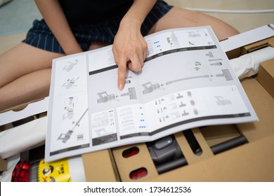 PENANG, MALAYSIA - MAY 12, 2020: Lady's hand pointing at the user manual of the brand new Dyson Cyclone V10 Fluffy vacuum cleaner during the open box.