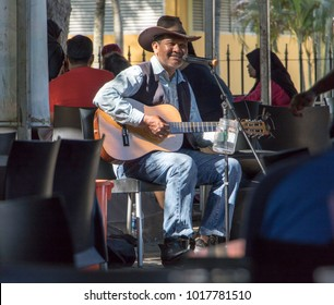PENANG, MALAYSIA, NOV 13 2017, Guitarist while playing guitar in the outdoor restaurant. Country singer with acoustic guitar. A man is playing a guitar at an outdoor party.
