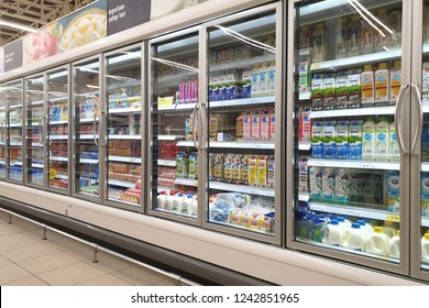 PENANG, MALAYSIA - NOV 21, 2018: Interior view of huge glass freezer with various brand cold beverage and dairy products in Tesco hypermarket. Tesco is the third largest retailer stores worldwide.