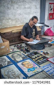 Penang,  Malaysia.  September 8, 2018: Middle aged artist draws and sells graphic art on street market Georgetown.