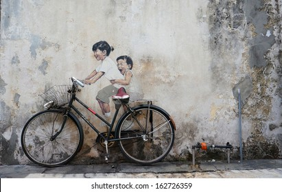 PENANG, MALAYSIA-AUG 13: A mural 'Little children on a bicycle painted by Ernest Zacharevic in Penang on Aug.13, 2013. Thisl is one of the 9 murals painted by him in early 2012.