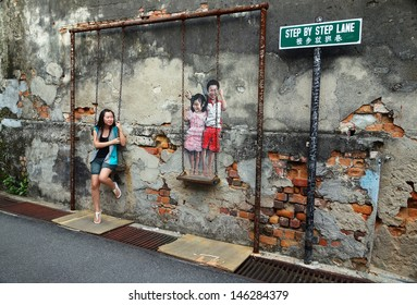 PENANG, MALAYSIA-JULY 6: Local tourist poses on Street Mural installation tittle 'Children on the Swing' painted by Louis Gan in Penang on July 6, 2013.