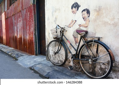 PENANG, MALAYSIA-JULY 6: Street Mural Installation Painting tittle 'Little Children on a Bicycle' painted by Ernest Zacharevic in Penang on July 6, 2013.