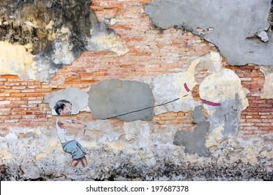 PENANG, MALAYSIA-MAY 12: Street art titled Little Boy with Pet Dinosaur by Ernest Zacharevic in Penang on May 12, 2014. It was a Mirrors George Town project for the 2012 George Town Festival.