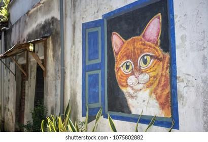 Penang Street Art, Georgetown, Penang, Malaysia - October 2016: World famous street art with big cat inside open window wall