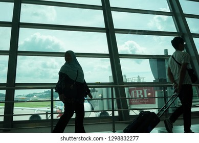 Penang,Malaysia - 04-01-2019 : tourist walking with luggage by the windows in Penang International Airport when heading to London from Malaysia.