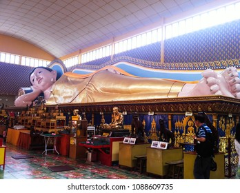 PENANG/MALAYSIA - DECEMBER 10, 2013: tourists are visiting the reclining Buddha statue inside decorated and famous thai buddhist temple in a daylight