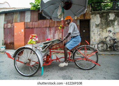 PENANG,MALAYSIA - JUNE 10,2016 : Indian people ride tribike for service tourist people in front of 3D art in georgetown Penang ,Malaysia.