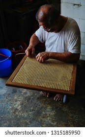Penang,Malaysia-February 17th,2019:An old man weaving rattan chair the traditional way.He is one of the man who is restoring and fabricating rattan chairs in Chulia street.