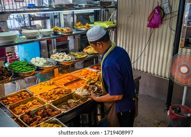 Penang,Malaysia-November 19th,2018:A man were seen filling gravy and dishes onto the plate of rice.This is called Nasi Kandar and a famous food in Penang.