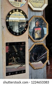 Penang,Malaysia-November 3rd,2018:A man was in frame among the wall mirrors hang in front of a shop.We can find few traditional making mirror shop on Penang.