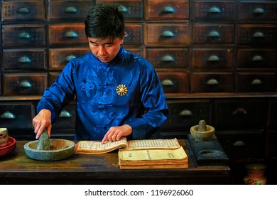 Penang,Malaysia-October 6th,2018:A chinese medicine practitioner is preparing herb according to his old medicine book.Chinese medicine is belived to start thousnd year back.