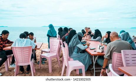 Penarik, Terengganu / Malaysia - June 8th 2019: A family is enjoying themselves eating seafood at the beach of Pantai Penarik. A favourite tourist spot with nice beach and delicious seafood