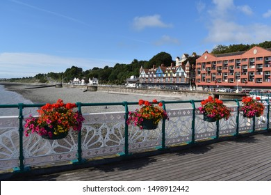 Penarth, Glamorgan, Wales- August 9th 2019:Penarth Pier with white cast iron work and hanging basket. On the beach front there are modern flats and painted period houses.
