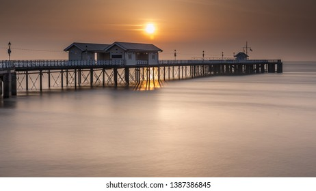 Penarth Pier, on the south Wales coast, near Cardiff, at sunrise. The sky is orange, and the sea is smooth