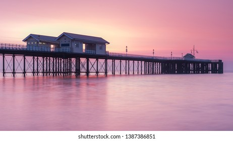 Penarth Pier, on the south Wales coast, near Cardiff, at sunrise. The sky is red and orange, and the sea is smooth