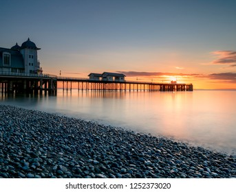Penarth pier from the pebble shoreline at sunrise.