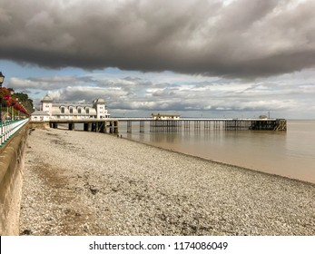 PENARTH, VALE OF GLAMORGAN - AUGUST 2018: Wide angle view of the shoreline and pier in Penarth, Wales, under a large dark cloud.