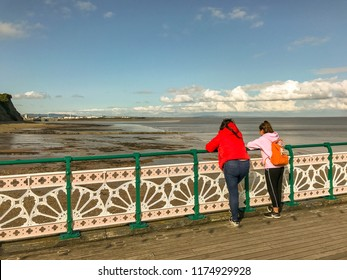PENARTH, VALE OF GLAMORGAN - AUGUST 2018: Two young people on the pier in Penarth in the Vale of Glamorgan landing on the decorative metal railings looking out over the shoreline.